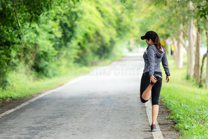 Healthy smiling woman warming up stretching her arms and looking away in the road outdoor. Asian runner woman workout before fitne royalty free stock image