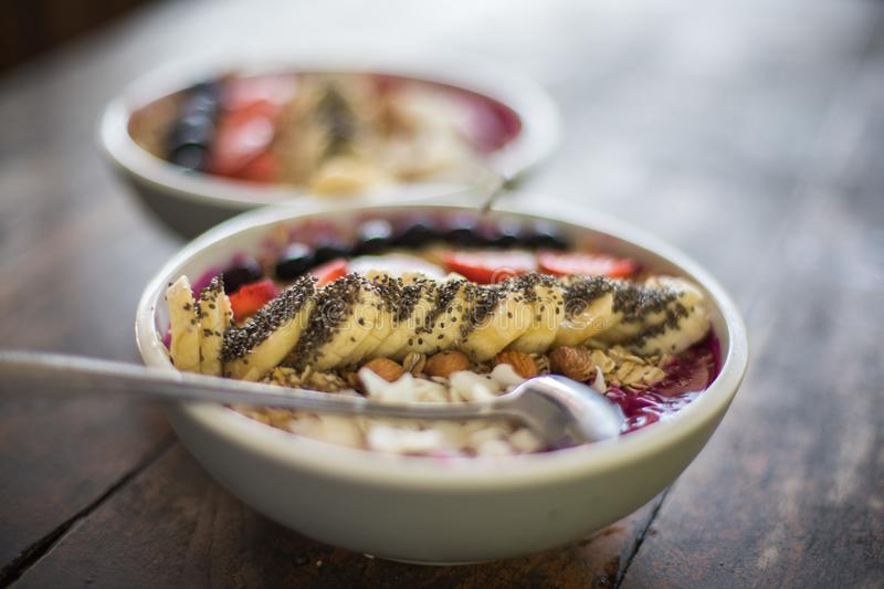 Healthy smoothie bowl for breakfast. On tropical island Bali, Indonesia. This healthy smoothie bowl contains chia seeds, banana, dragon-fruit, blackberries royalty free stock photos