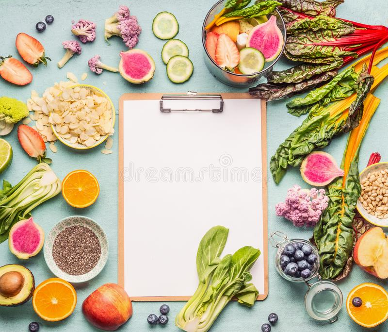 Healthy smoothie ingredients around clipboard with blank paper sheet on light table, top view, frame. Various fruits , vegetables royalty free stock photos