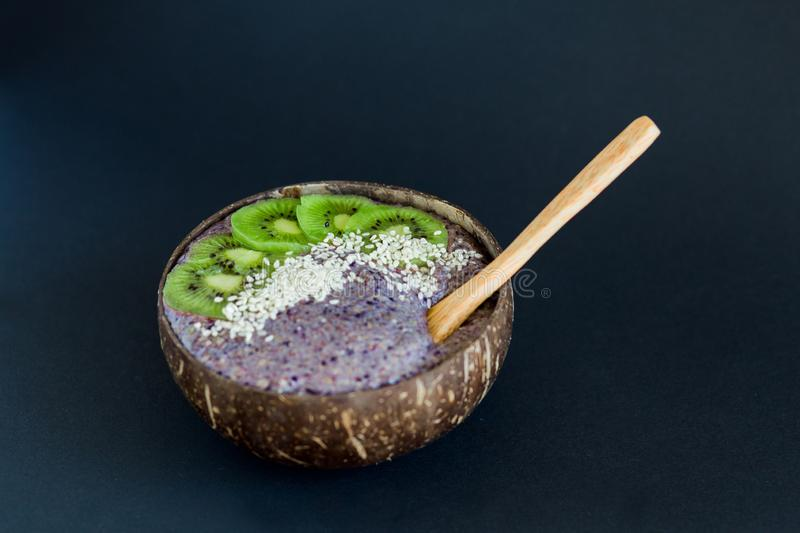 Healthy smoothie , plate made from coconut shell on dark background royalty free stock images