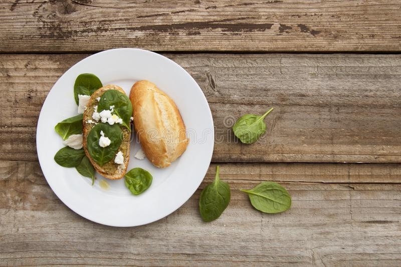 Healthy snack. Bun or bread with pesto pasta and basil leaves. Rustic wooden table, top view. stock photos