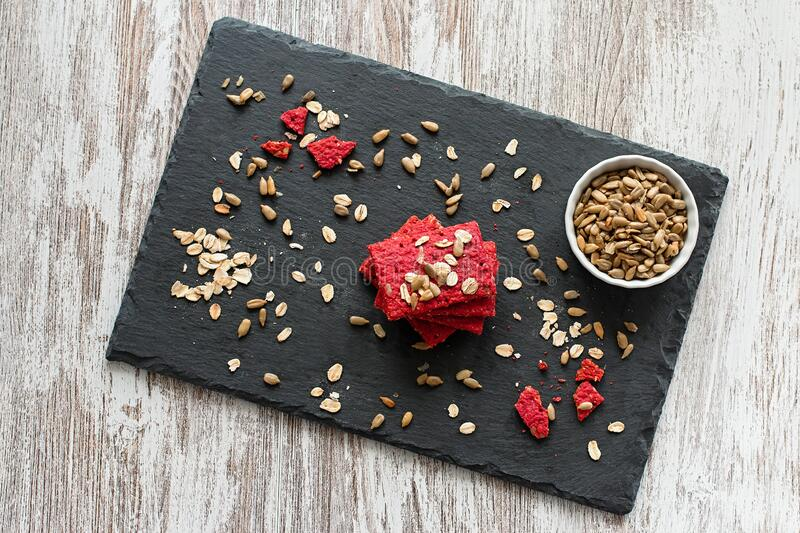 Healthy snack cracker or biscuit with seeds and beetroot top view on a stone plate with oat flakes on wooden background stock images