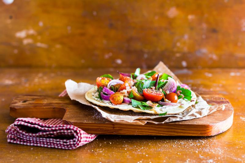 Healthy snack with fresh homemade tortilla, cream cheese sauce, chard leaves, cherry tomatoes, onion served on a wooden cutting bo. Ard, selective focus. Image stock photography