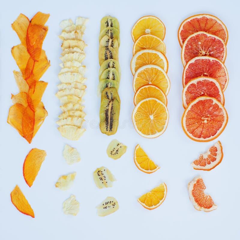 Healthy snack. Homemade dehydrated fruit chips on white background. Dry orange, grapefruit, mango, banana, kiwi. Diet food. square stock image
