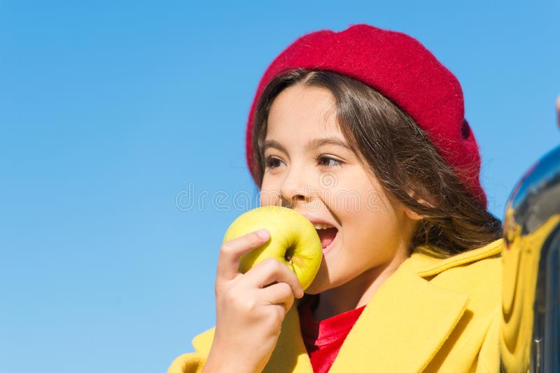 Healthy snack for a kid. Cute child eating healthy fruit on sunny day. Little girl biting into juicy green apple for royalty free stock photos