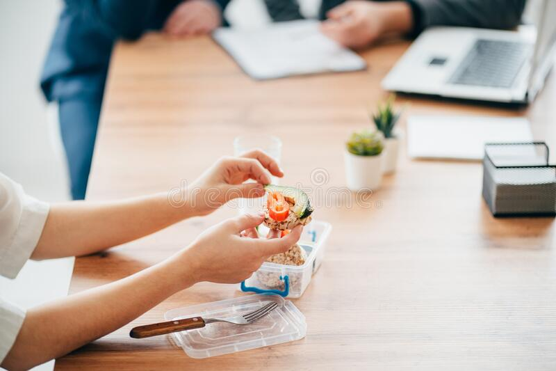 Healthy snack at office, lunch break. Healthy snack at office. Woman eating food from take away lunch box during lunch break. Proper nutrition at office stock images