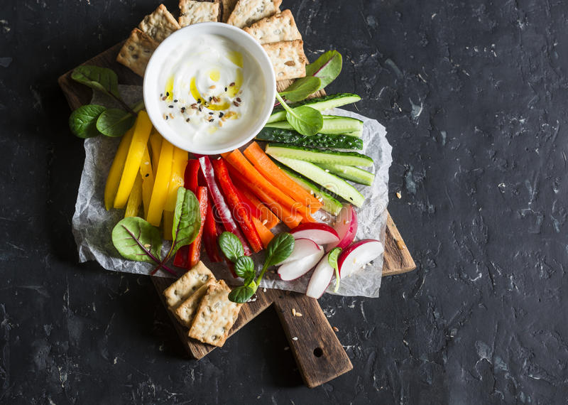 Healthy snack - raw vegetables and yogurt sauce on a wooden cutting board, on a dark background, top view. Vegetarian healthy food stock image