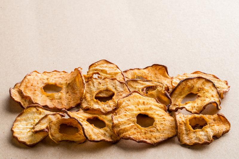Healthy snack. Tasty dried apple and pear rings chips on light b stock photos