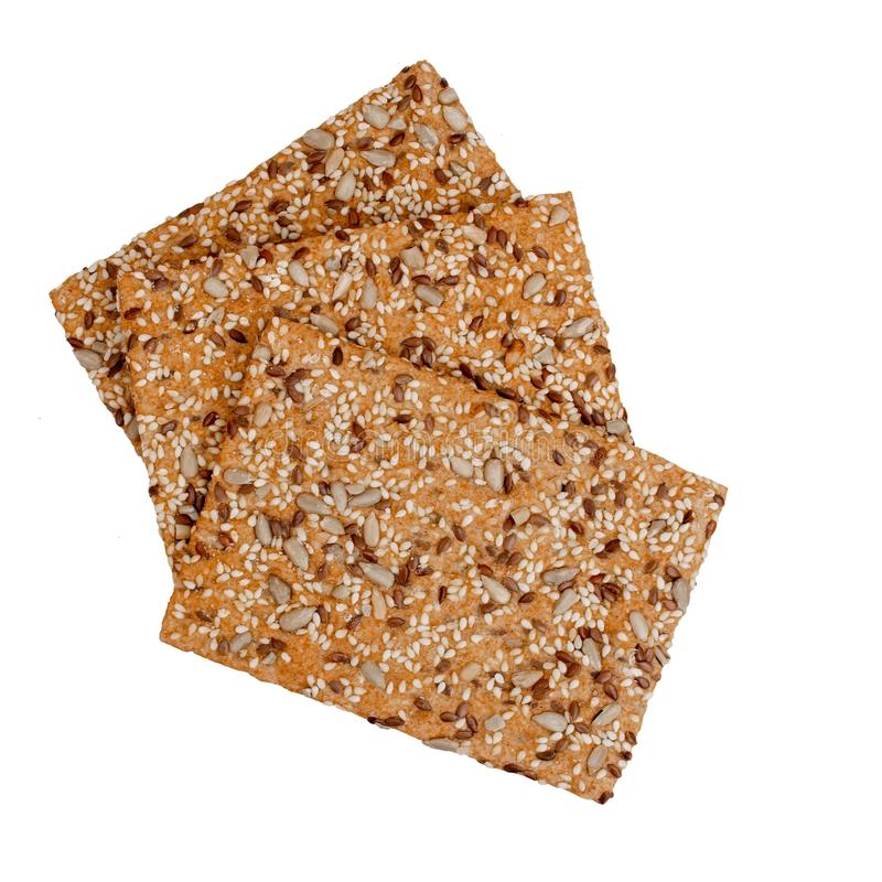 Healthy snack, wholemeal, wholewheat crackers with sunflower, linseed and sesame seeds. Isolated on white background. stock photos