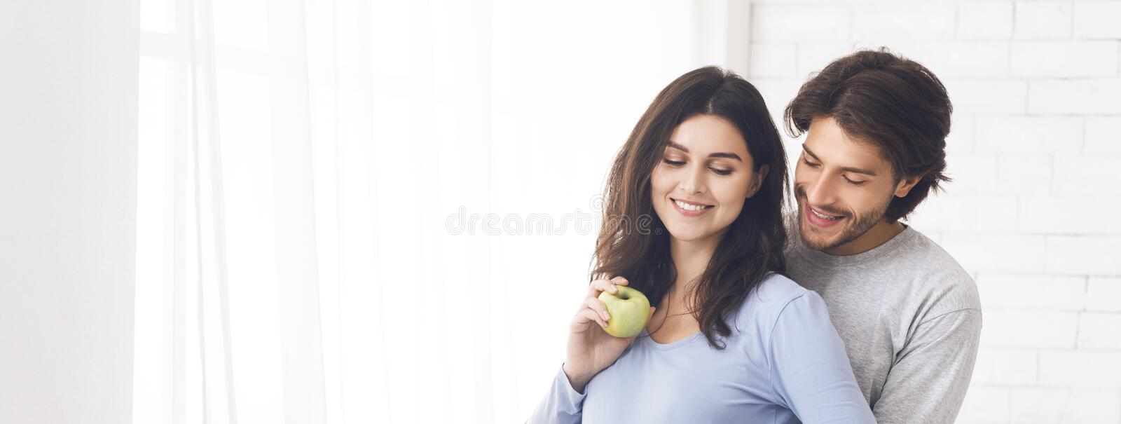 Young happy couple cuddling near window at home, woman holding apple royalty free stock image