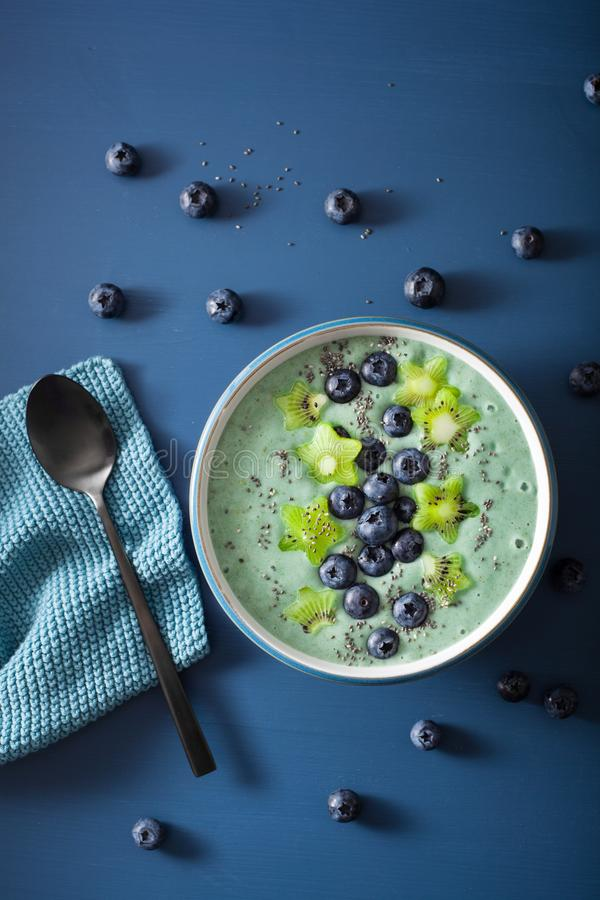 Healthy spirulina smoothie bowl with blueberry, kiwi stars, chia seed stock photography