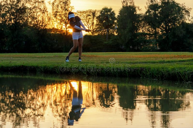 Healthy Sport. Asian Sporty woman golfer player chips and swing golf on the green sunset evening time, she presumably does exercis stock image