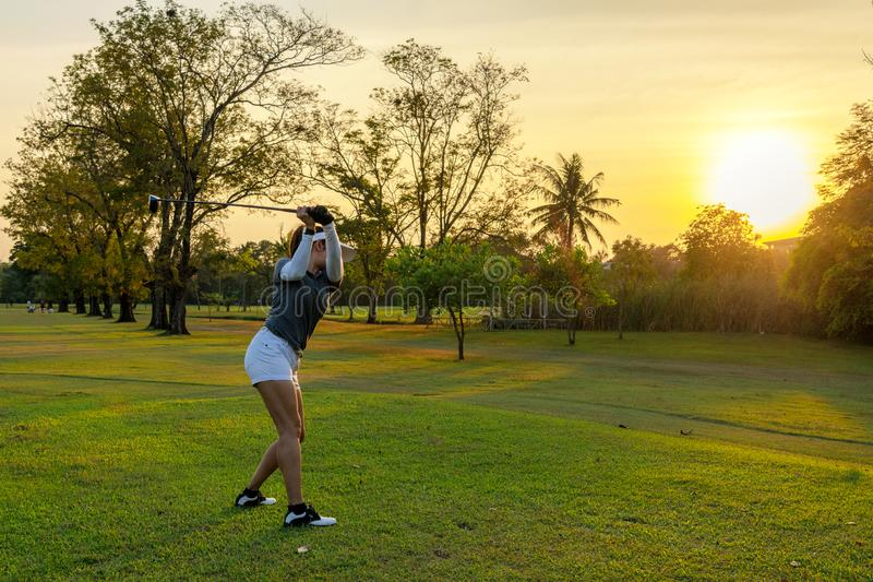 Healthy Sport. Asian Sporty woman golfer player doing golf swing tee off on the green course evening time, she presumably does exe royalty free stock photos