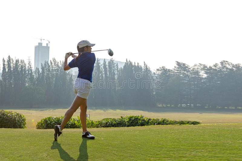 Healthy Sport. Asian Sporty woman golfer player doing golf swing tee off on the green evening time royalty free stock image
