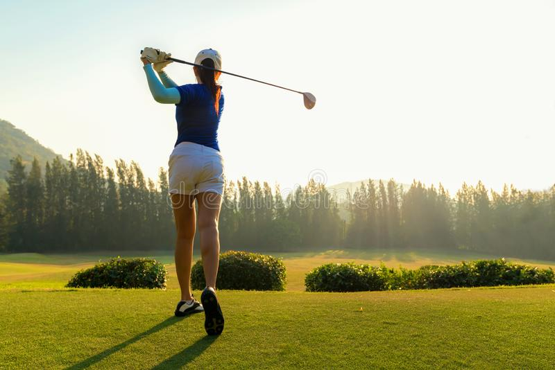 Healthy Sport. Asian Sporty woman golfer player doing golf swing tee off on the green evening time, she presumably does exercise. Healthy Lifestyle Concept royalty free stock images