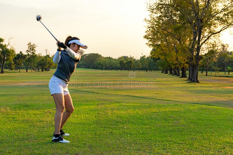 Healthy Sport. Asian Sporty woman golfer player doing golf swing tee off on the green evening time, she presumably does exercise. Healthy Lifestyle Concept stock photos