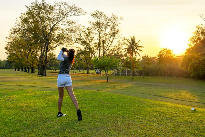 Healthy Sport. Asian Sporty woman golfer player doing golf swing tee off on the green evening time, she presumably does exercise. stock image