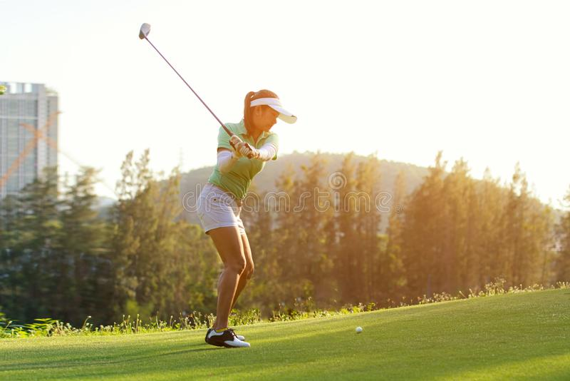 Healthy Sport. Asian Sporty woman golfer player doing golf swing tee off on the green, people presumably does exercise. royalty free stock image