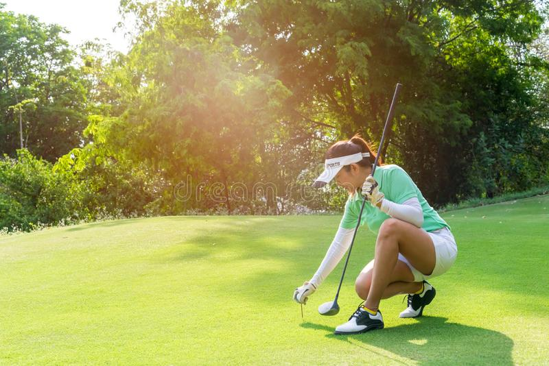 Healthy Sport.  Asian sporty woman putting golf ball on tee with club in golf course on evening on time for healthy sport. stock images