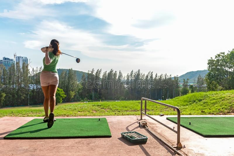 Healthy Sport.  Asian sporty woman swing golf ball practice at golf driving range on evening on time for healthy sport. royalty free stock images