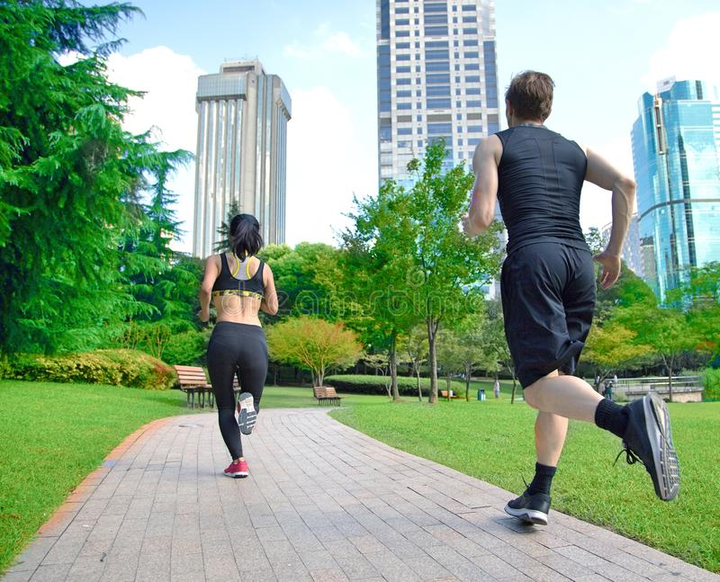 Healthy sports people trail running living an active life. Happy lifestyle couple of athletes training cardio together in summer stock photography