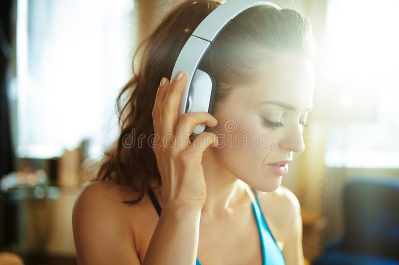 Healthy sports woman listening to music with headphones. Healthy sports woman in fitness clothes listening to the music with headphones in the modern living room stock photography