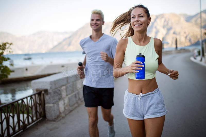 Healthy sporty lifestyle. Happy fit people friends exercising and running outdoor royalty free stock images