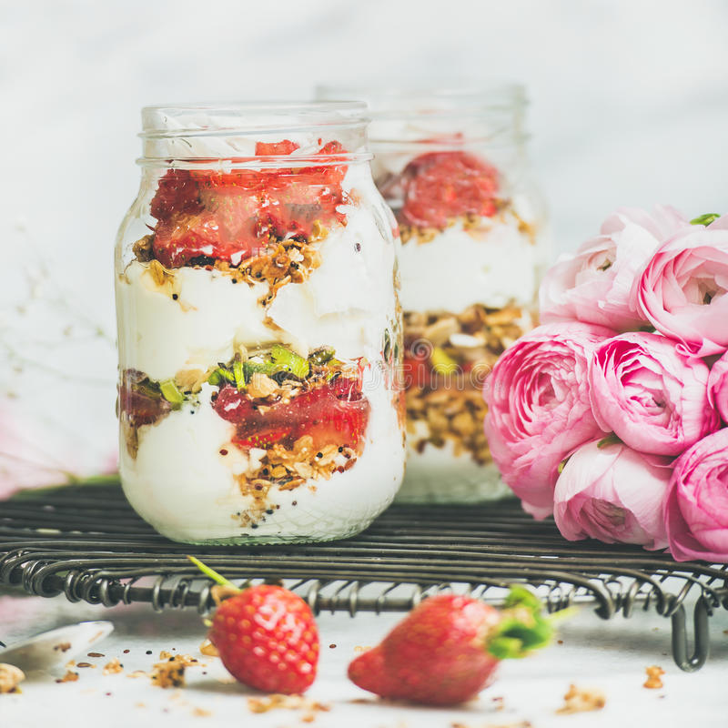 Healthy spring breakfast jars with pink raninkulus flowers, clean eating stock image