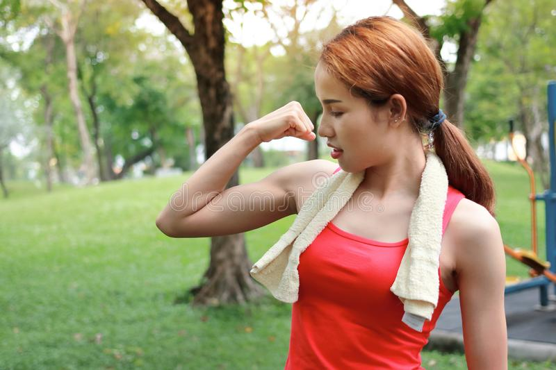 Healthy strong Asian woman in red sportswear showing her hands in natural park. Fitness and lifestyle concept stock photo