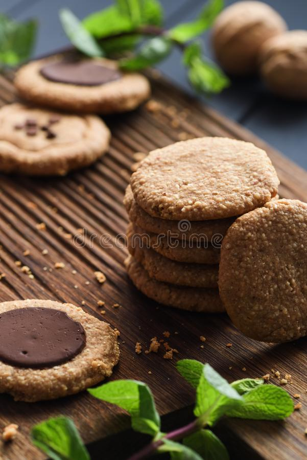 Healthy sugar free gluten free vegetarian sweets. Peanut butter cookies with dark chocolate drops served with raw mint on dark oak royalty free stock images