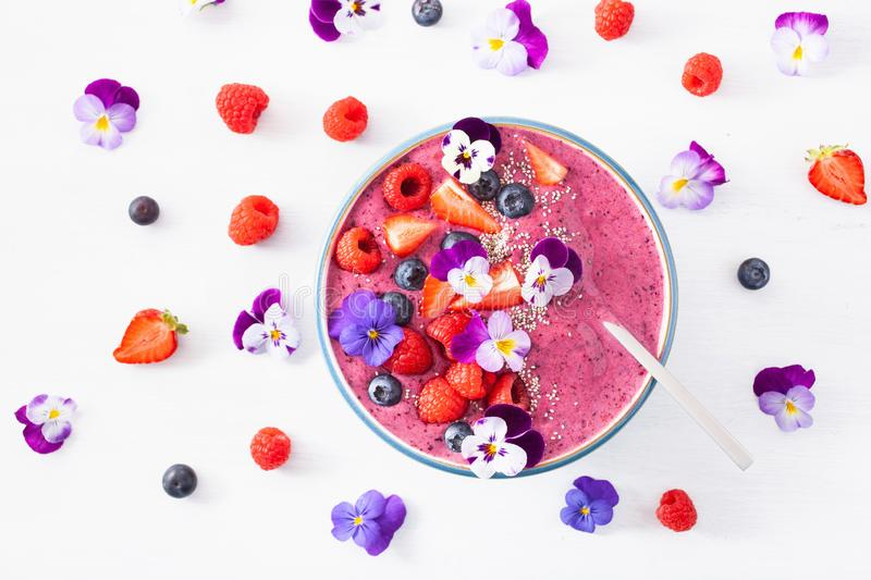 Healthy summer berry smoothie bowl with flowers and chia seed stock photography