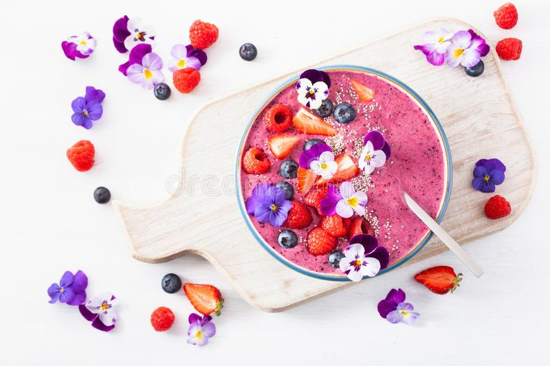 Healthy summer berry smoothie bowl with flowers and chia seed royalty free stock images