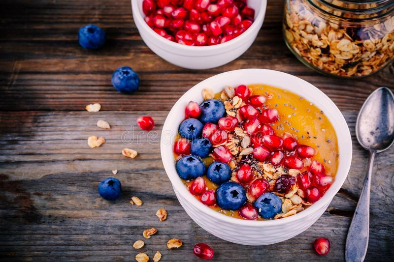Healthy summer breakfast mango smoothie bowl with granola, blueberries, pomegranate and chia seeds stock images