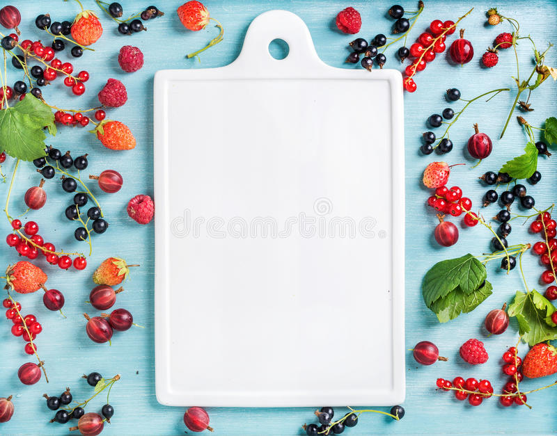 Healthy summer garden berry variety. Black and red currant, gooseberry, rasberry, strawberry, mint leaves on blue stock image