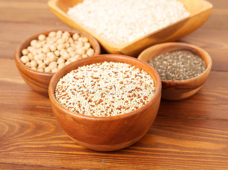 Healthy super food - dry chickpeas, quinoa, chia on brown wooden background, side view. Healthy super food - dry chickpeas, quinoa, chia on a brown wooden stock photo
