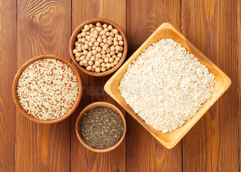Healthy super food - dry chickpeas, quinoa, chia on brown wooden background, top view. Healthy super food - dry chickpeas, quinoa, chia on a brown wooden stock photo