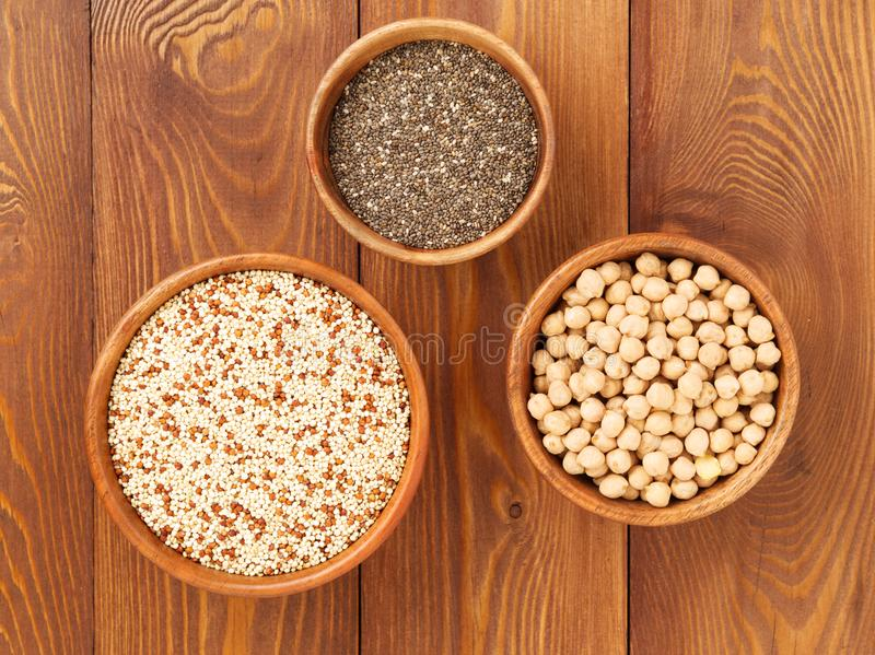 Healthy super food - dry chickpeas, quinoa, chia on brown wooden background, top view. Healthy super food - dry chickpeas, quinoa, chia on a brown wooden stock photography