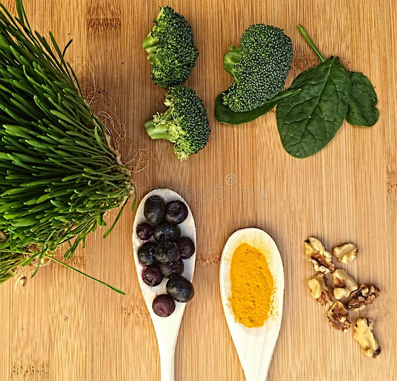 Still Life of wheat grass, spinach, acacia berries, nuts and broccoli royalty free stock images