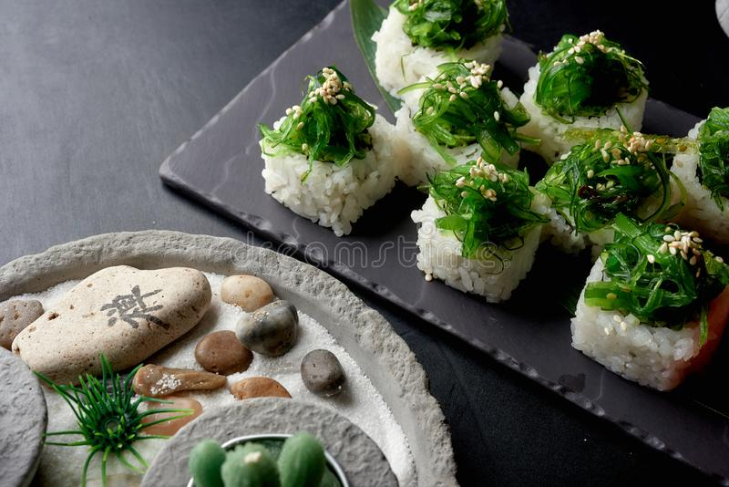 Healthy sushi rolls with wakame on top on dark stone table. royalty free stock photography