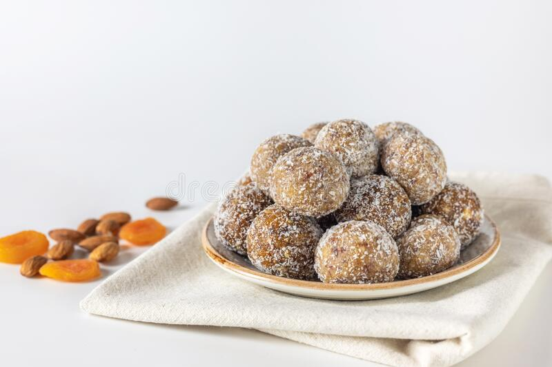 Healthy sweet food. Energy balls in a plate on a white background. Homemade energy balls with dried apricots, raisins, dates, prunes, walnuts, almonds and stock image