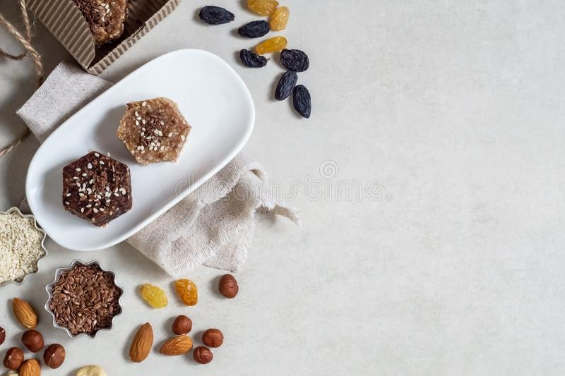 Healthy sweets made from natural ingredients on a white plate. Near nuts, sesame and raisins. Healthy foodrr stock images