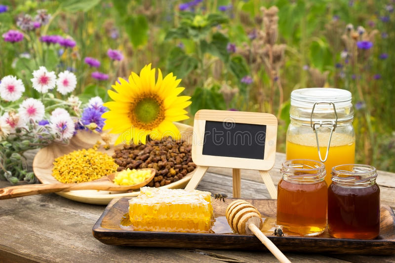 Healthy Sweets. A slate between different beekeeping products on a wooden table royalty free stock images
