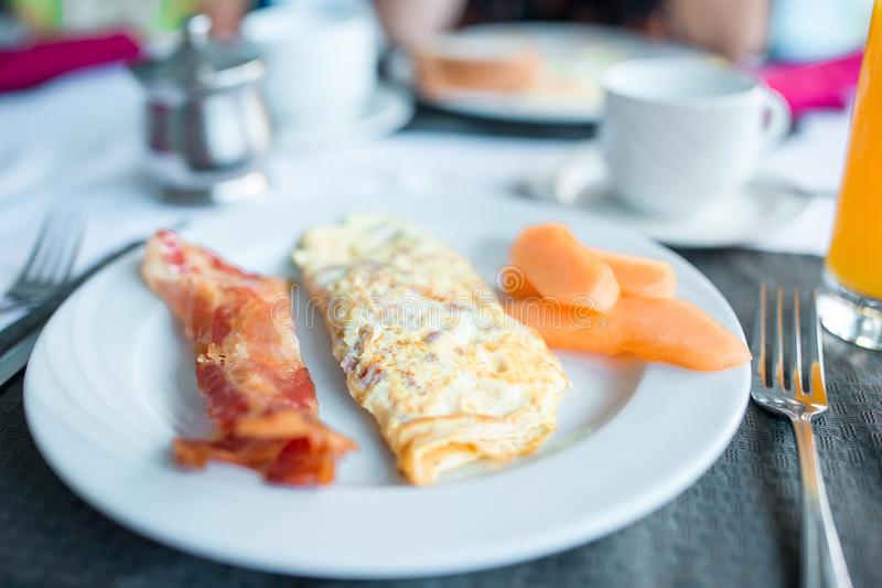Healthy tasty american breakfast with omlette and bacon on table in cafe. Healthy tasty breakfast on table in cafe stock image