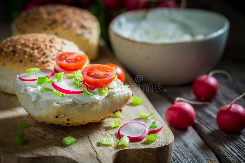 Healthy and tasty sandwich with fromage cheese and cherry tomatoes. On wooden table stock image