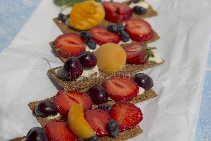 Healthy and tasty toasts with curd cheese, fruits and berries on a white parchment paper stock photos