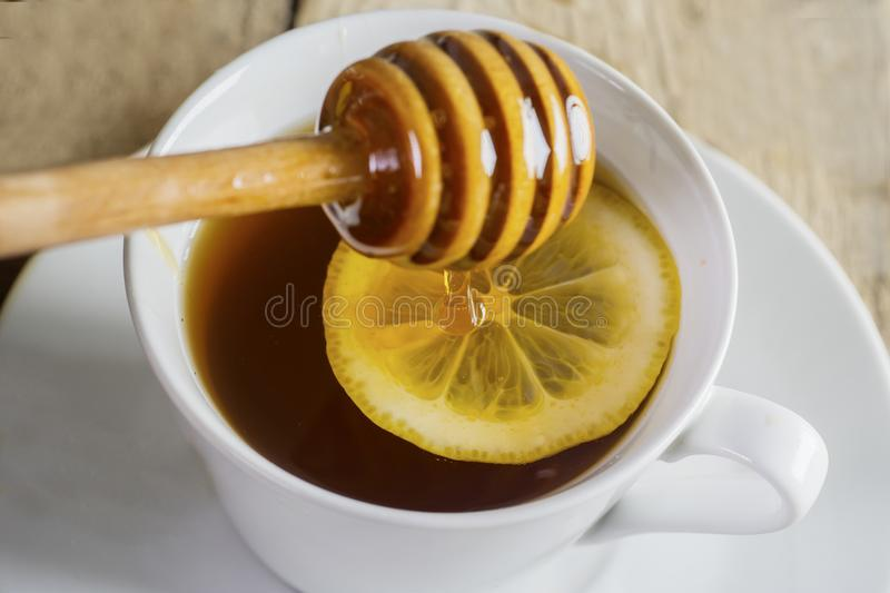 Healthy tea with lemon and honey. Closeup of healthy tea with slice of lemon and honey. Shot above wooden table royalty free stock photo