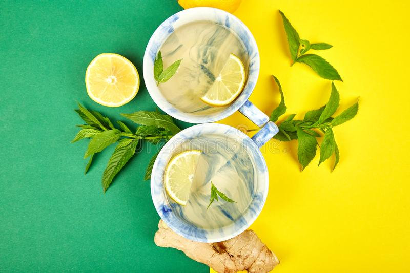 Healthy tea two cups with lemon, ginger, mint. On a color background. Warm drink for cold flu winter fall days. Flat lay. Copy space. Top view stock images