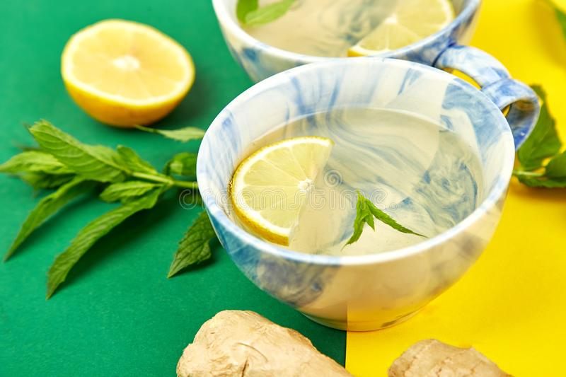Healthy tea two cups with lemon, ginger, mint. On a color background. Warm drink for cold flu winter fall days. Flat lay. Copy space. Top view stock photo
