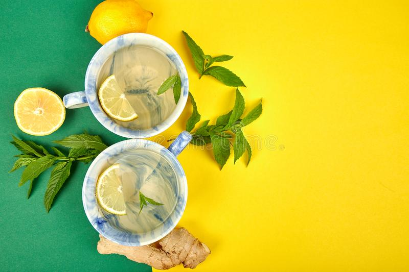 Healthy tea two cups with lemon, ginger, mint. On a color background. Warm drink for cold flu winter fall days. Flat lay. Copy space. Top view royalty free stock photos