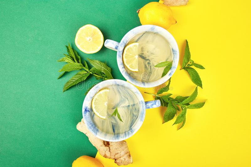 Healthy tea two cups with lemon, ginger, mint. On a color background. Warm drink for cold flu winter fall days. Flat lay. Copy space. Top view royalty free stock images